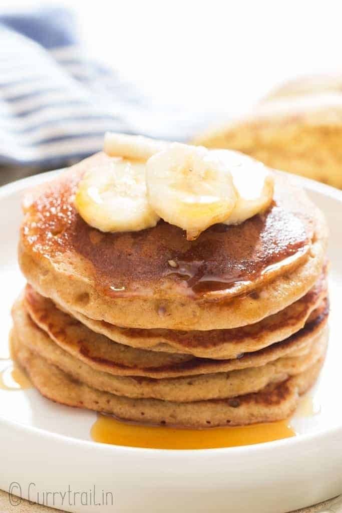 easy banana oatmeal pancake served with banana slices and maple syrup on ceramic plate