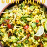 corn salad with avocados and cherry tomatoes in wooden bowl with text
