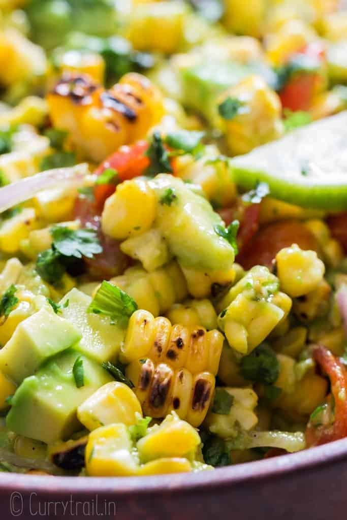 avocado corn tomato salad in wooden salad bowl with lime wedges