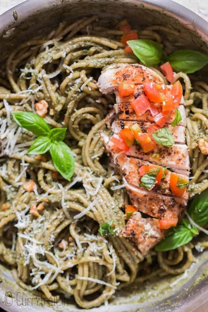 chicken pesto pasta with tomato salsa in skillet