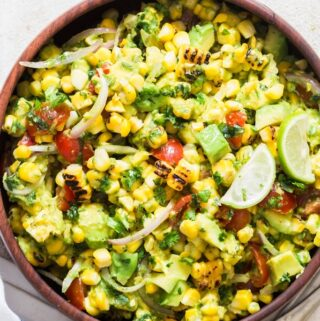 corn salad with avocados and cherry tomatoes in wooden bowl