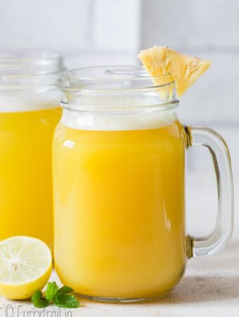 fresh homemade pineapple juice served with pineapple wedges in mason jars