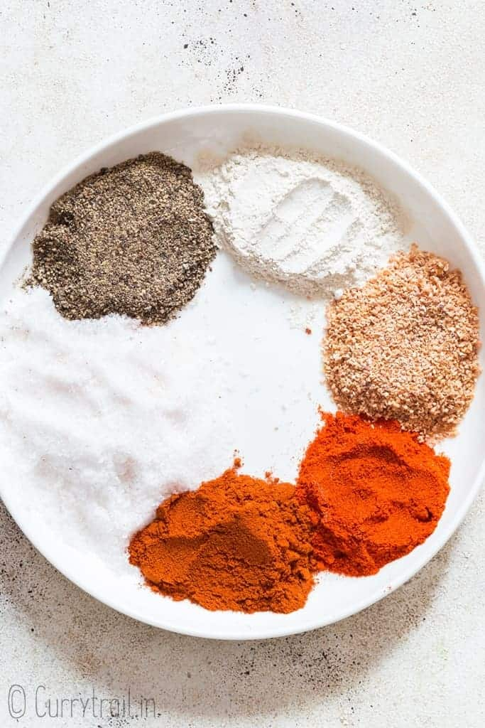 mixing in all spices to make seasoning salt on white ceramic plate