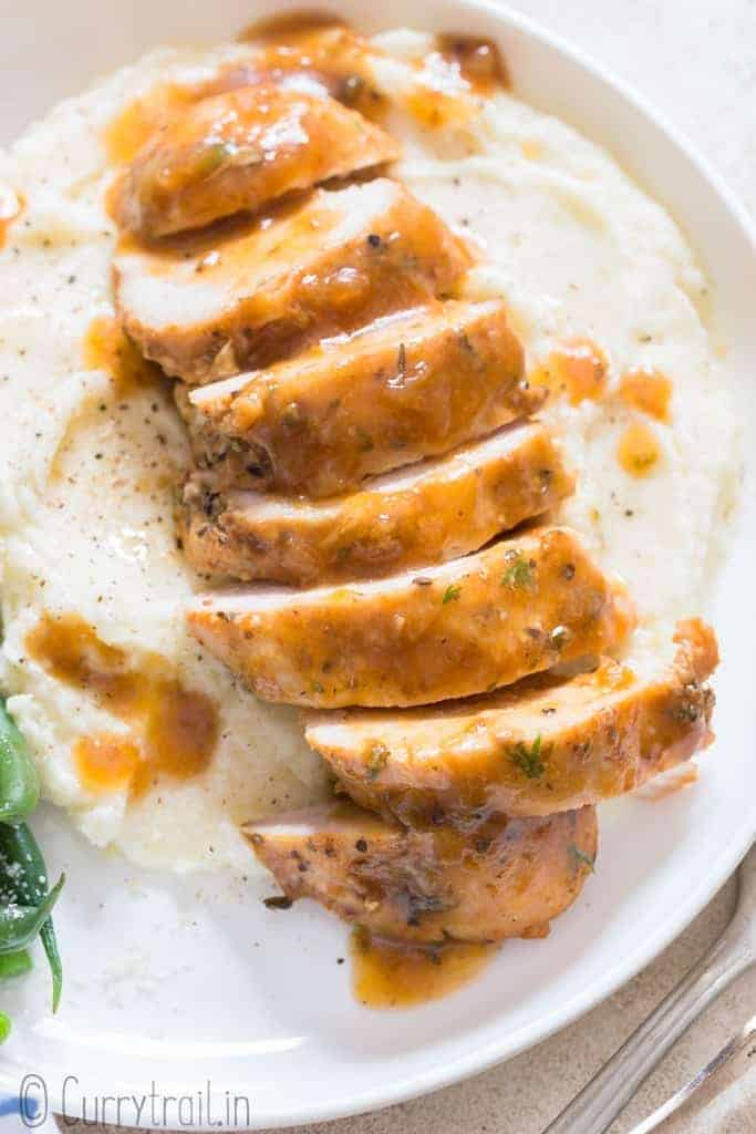 juicy chicken breasts cooked in instant pot served over mashed potatoes and green beans