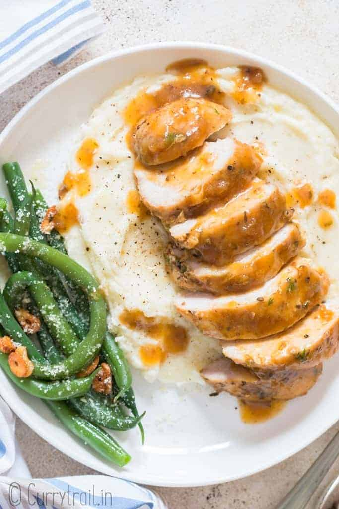 sliced instant pot chicken breasts served with mashed potatoes and sauteed green beans on white plate