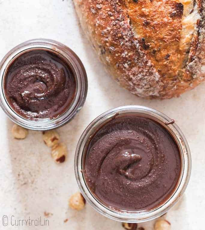 healthy homemade Nutella in two glass jars with sour dough bread loaf on side