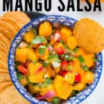 mango salsa with nachos in blue ceramic bowl with text