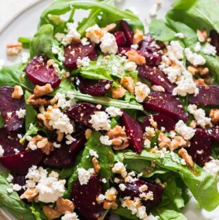 healthy arugula beetroot and feta cheese salad on white plate