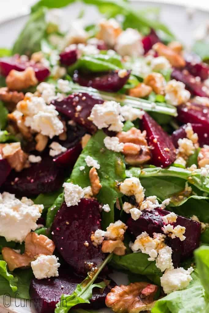 beet and feta salad with arugula leaves and walnuts on white plate