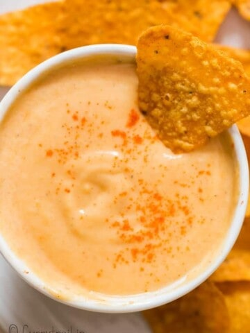 spicy nacho cheddar cheese sauce in small bowl with nachos on side