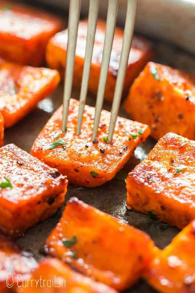 oven roasted sweet potatoes on baking tray garnished with parsley