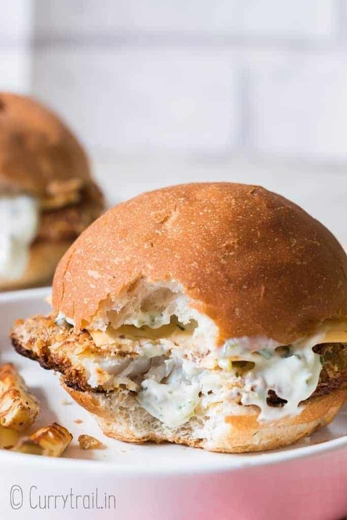 baked fish burger on white plate and red napkin