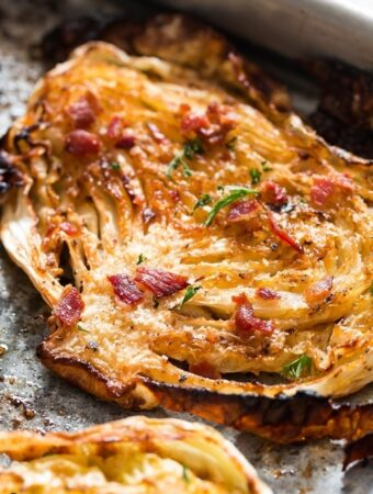 Cabbage steaks roasted in oven and garnished with Parmesan and bacon on baking tray