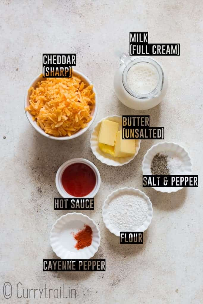 all ingredients for spicy nacho cheese sauce on white board