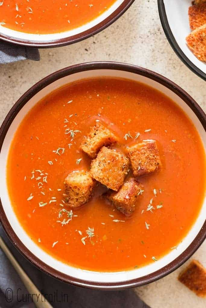 tomato basil soup in bowl served with croutons in bowls