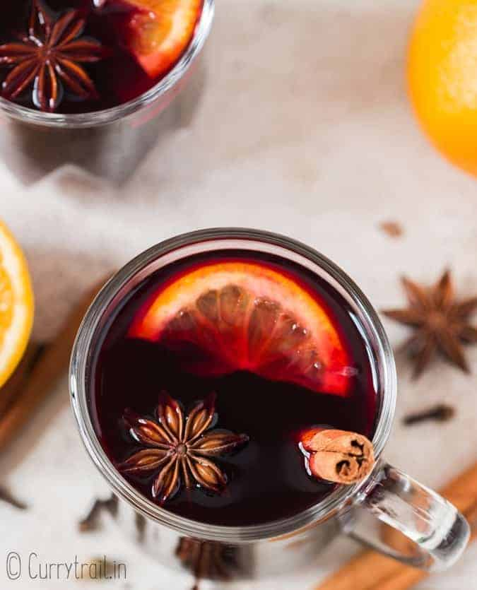 hot mulled wine in heat proof mugs with spices on sides