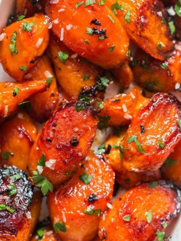 roasted glazed honey carrots with brown butter garlic in white servings dish