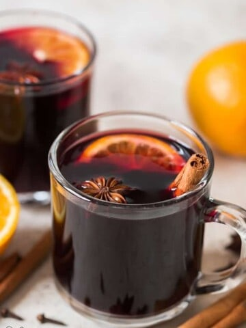 traditional mulled wine in heat proof mugs with spices on sides