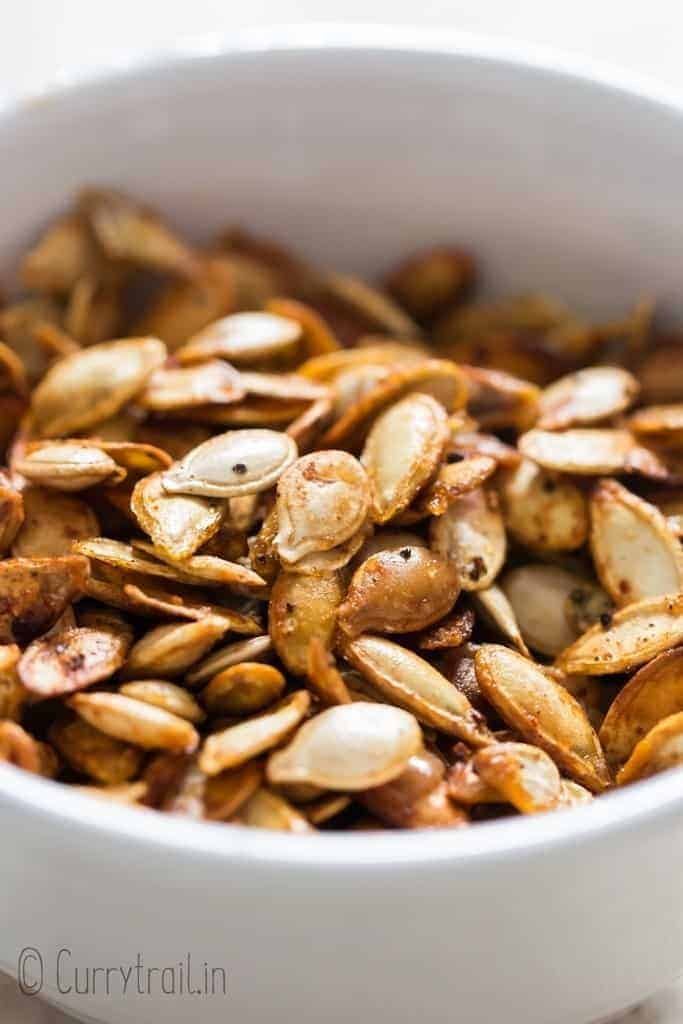 savory pumpkin seeds roasted in oven in ceramic bowl with text