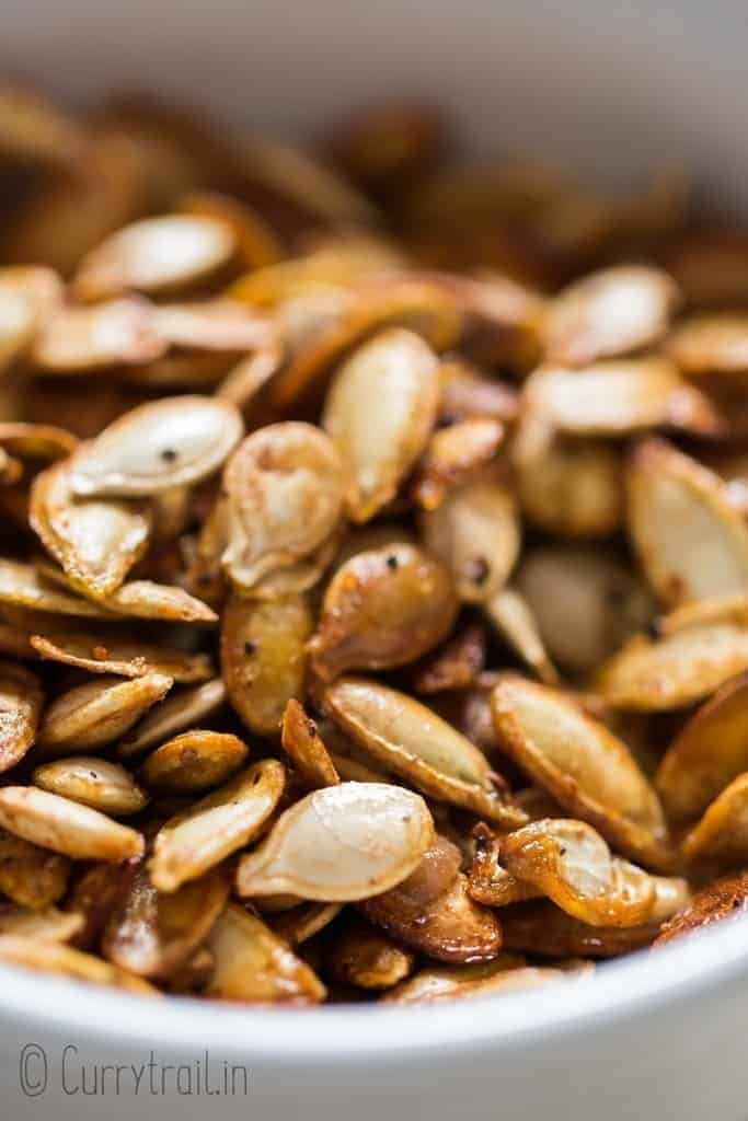 close up photo of savory roasted pumpkin seeds in ceramic bowl