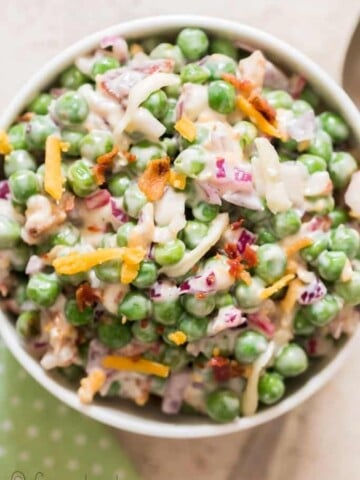pea salad with cheese, bacon and red onion in ceramic bowl