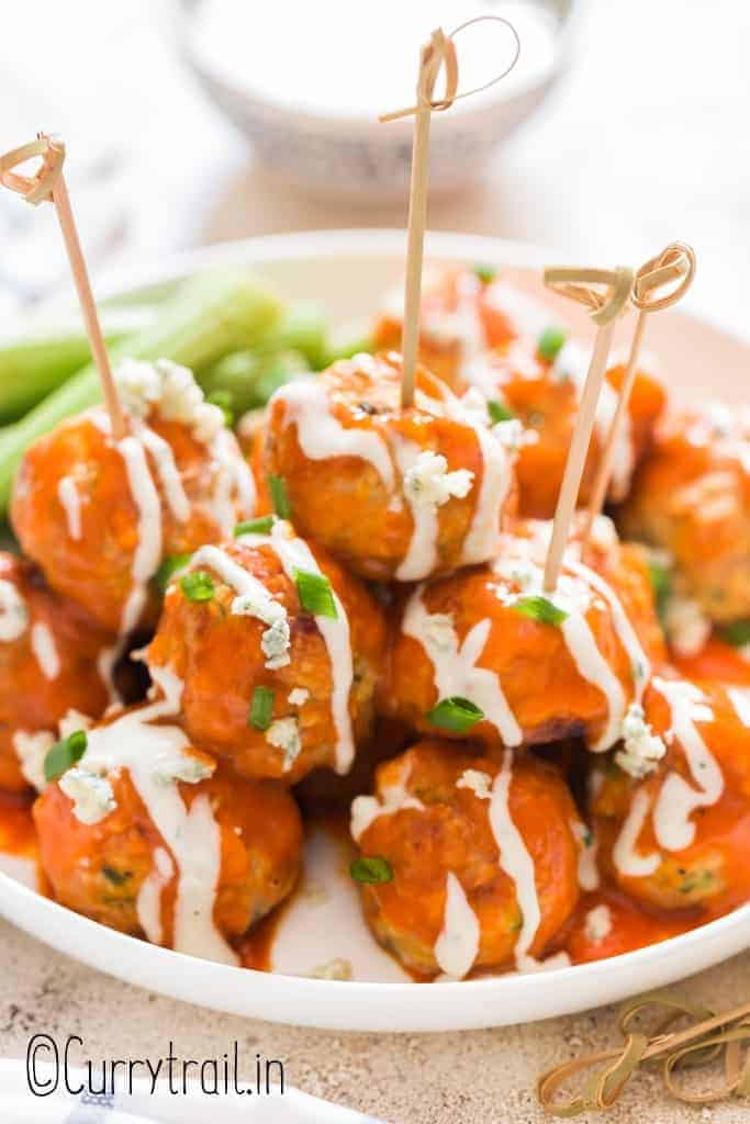 buffalo chicken meatballs stacked up on plate with blue cheese dressing on side