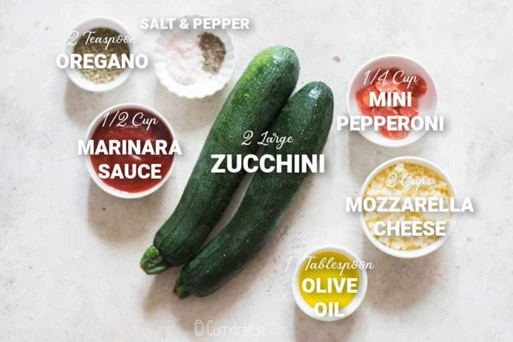all ingredients for zucchini pizza bites on white board