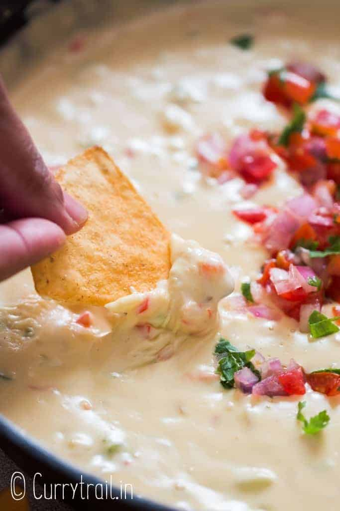 nacho dipped in warm white queso dip cooked in cast iron pan