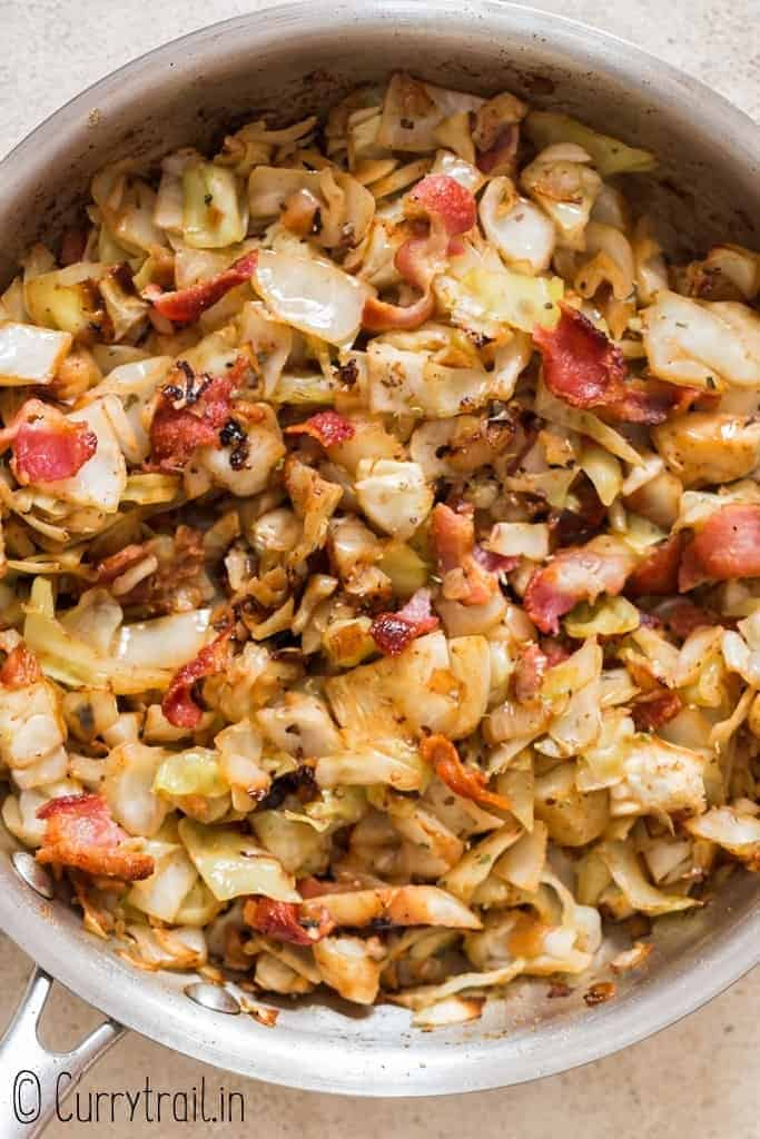 fried cabbage with bacon cooked in skillet