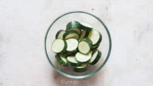 salting zucchini slices in bowl