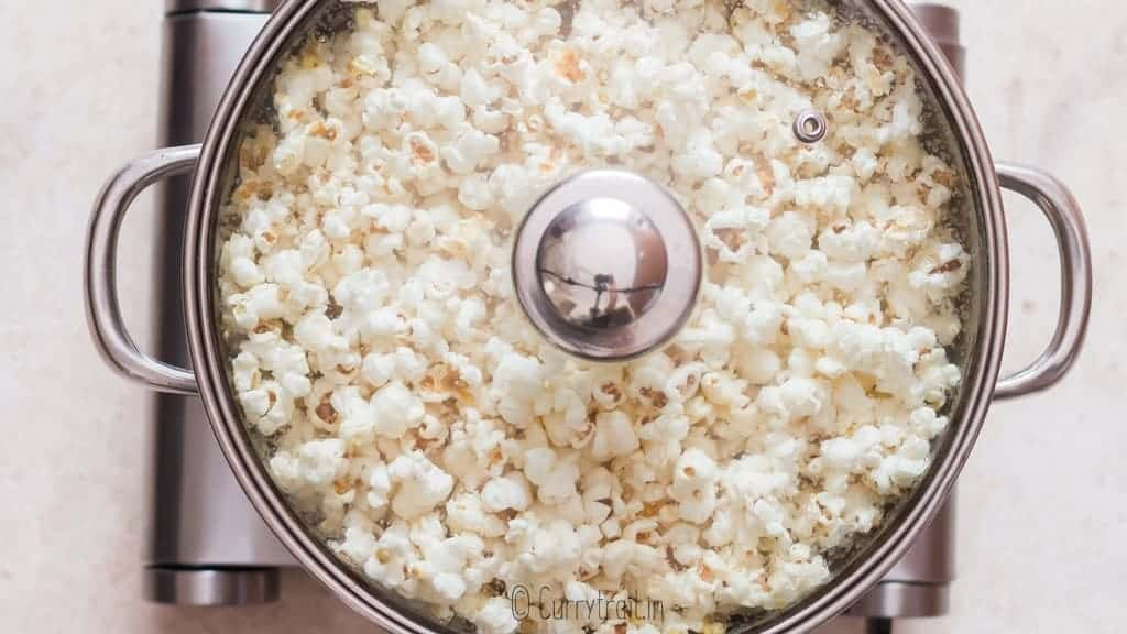 making homemade movie style popcorn in large pot with lid