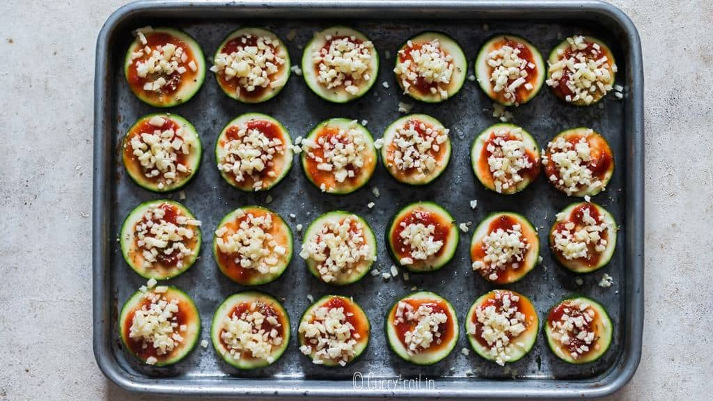 adding topping on zucchini slices for making pizza bites