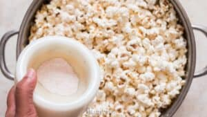 adding popcorn salt to freshly popped popcorn