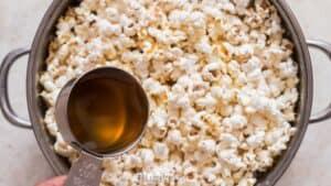 adding ghee to freshly popped popcorn