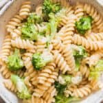 broccoli fusilli pasta served in ceramic bowl with lemon on side