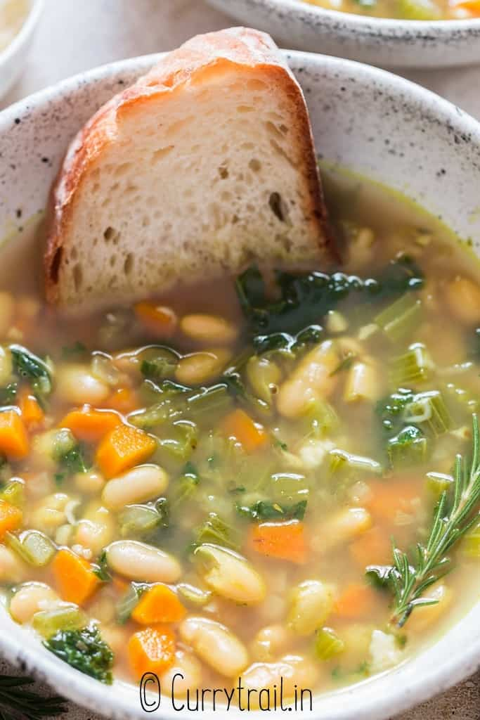 close up view of a bowl of white bean soup with bread