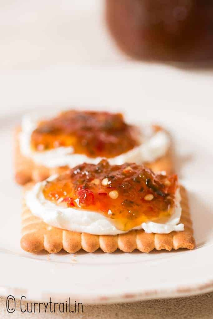 jar with jalapeno pepper jelly spread on cracker with cream cheese