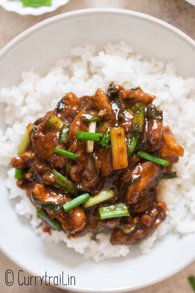 dark brown saucy Mongolian chicken served with rice in ceramic bowl