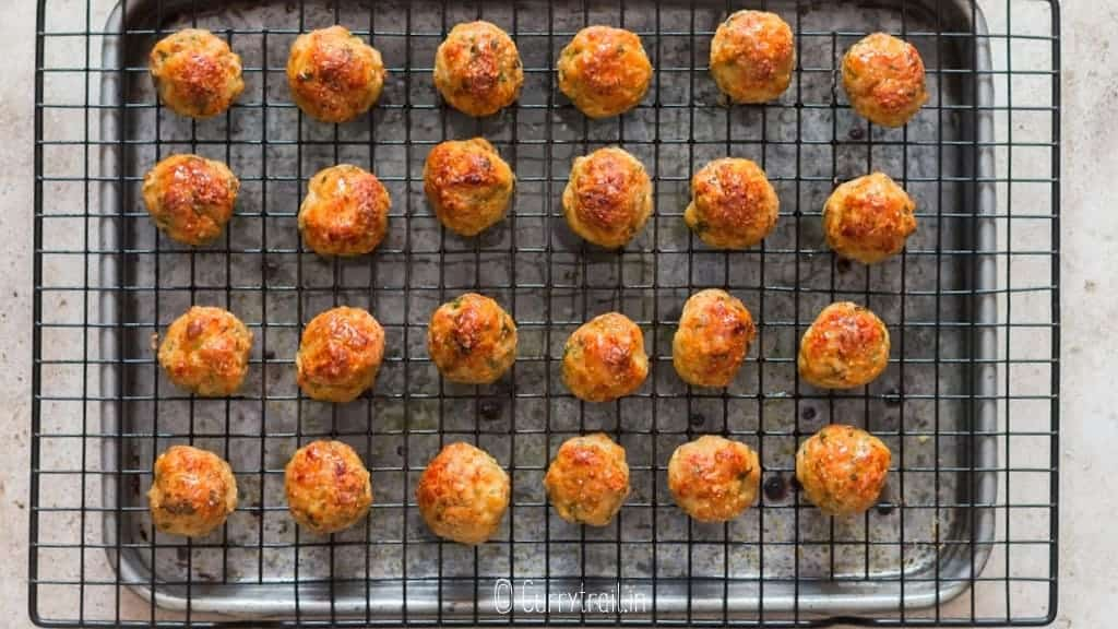 baked chicken meatballs on baking tray with wire rack