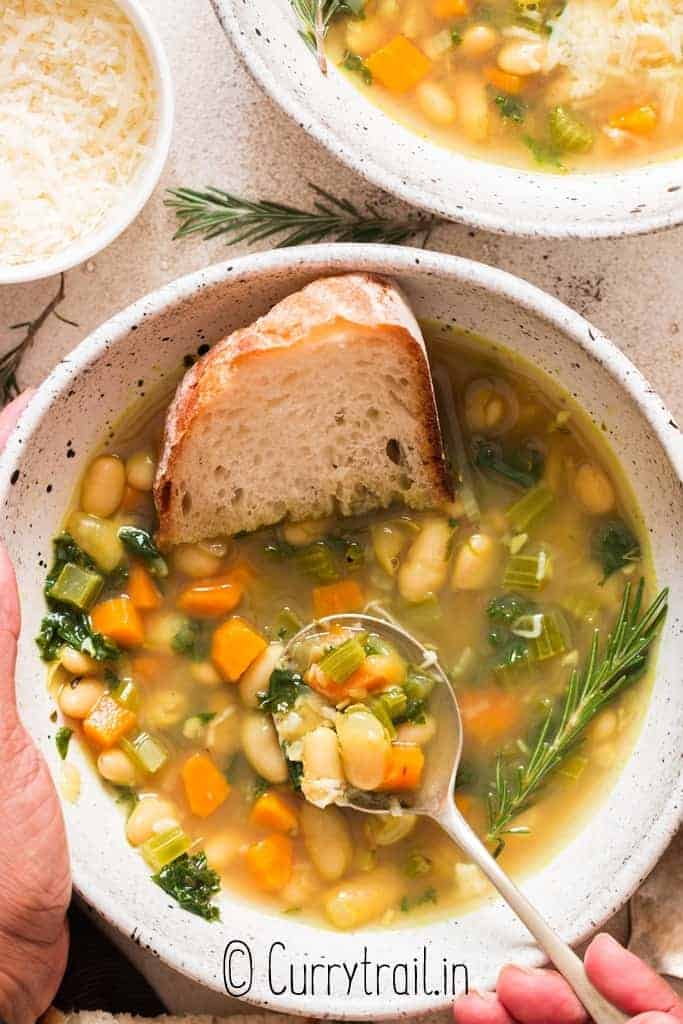 white bean and kale soup served in two ceramic bowl with crusty bread
