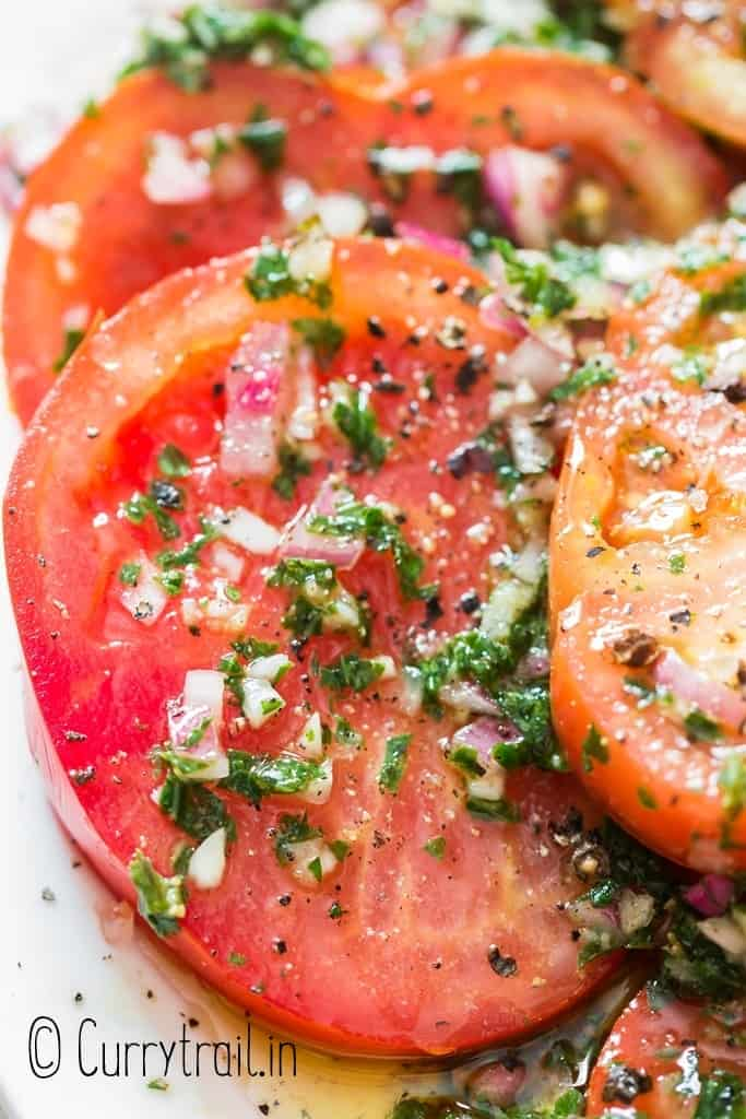 close up of tomatoes marinated in olive oil and herbs on plate