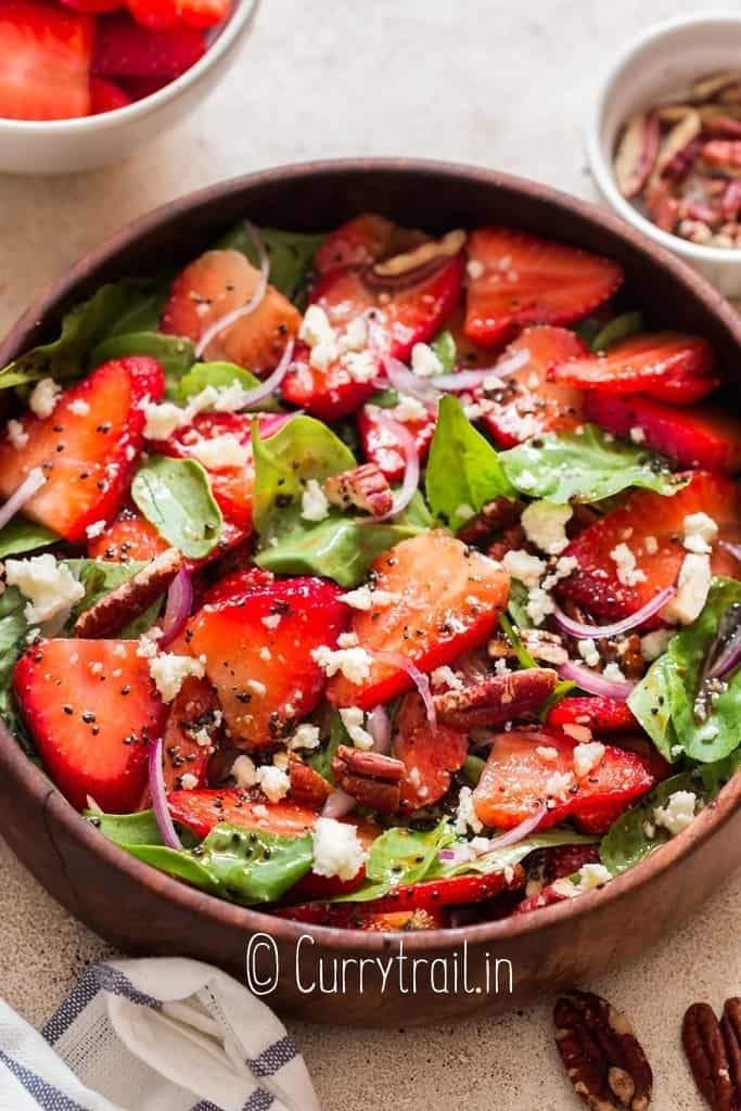 spinach and strawberry salad in wooden salad bowl