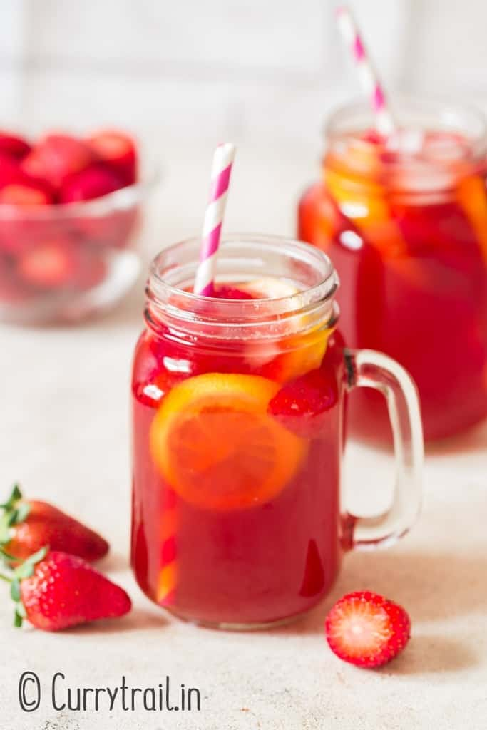 homemade southern sweet tea with strawberries in mason jugs