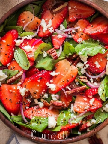 spinach and strawberry salad in wooden bowl with poppy seed dressing