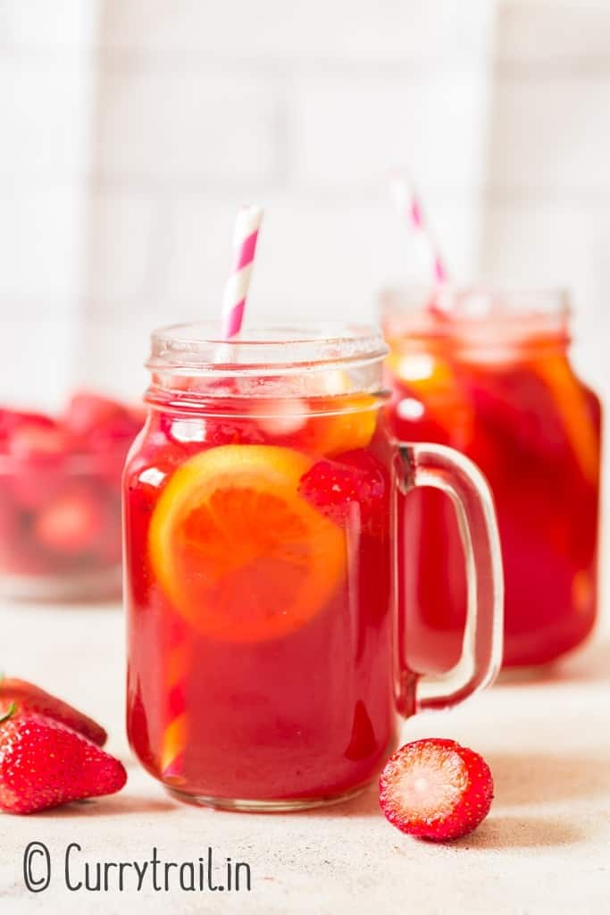 iced strawberry tea served in two mason jars
