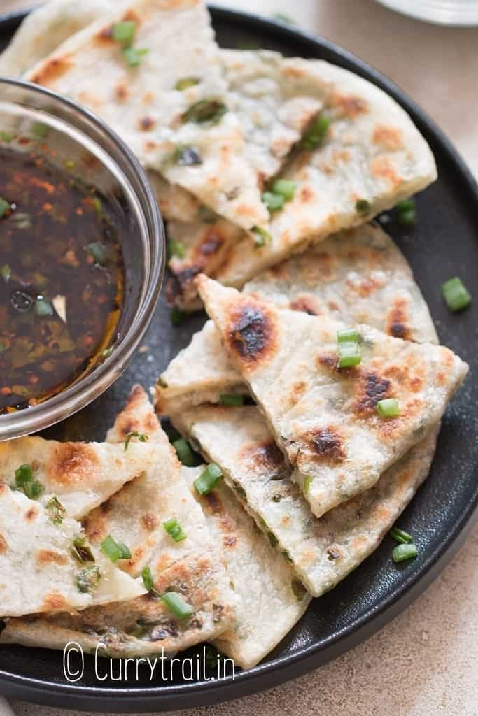 savory pancakes with scallion stuffing cut into triangles with dipping sauce