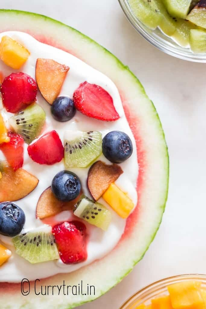 close up view of watermelon pizza with cheesecake frosting and fruits