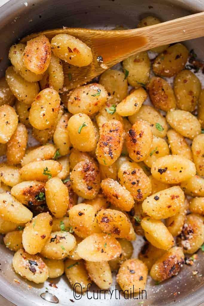 fried gnocchi in garlic butter sauce in skillet