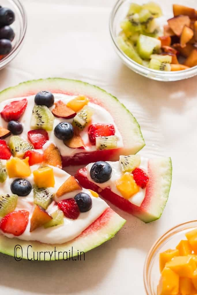 thick slice of watermelon pizza with cheesecake frosting and fruits