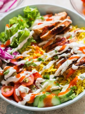easy chicken shawarma bowl with hummus dressing and red chili sauce